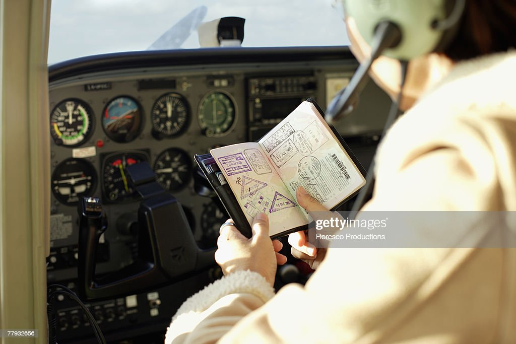 Pilot looking at passport in cockpit : Stock Photo