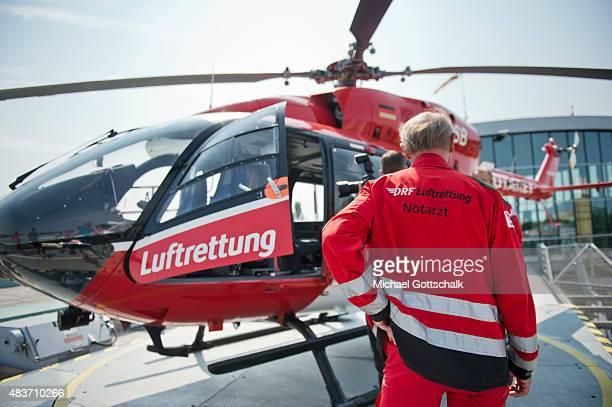 A pilot of DRF Deutsche Luftrettung stands in front of a medevac Helicopter or Rettungshubschrauber on August 12 2015 in Berlin Germany