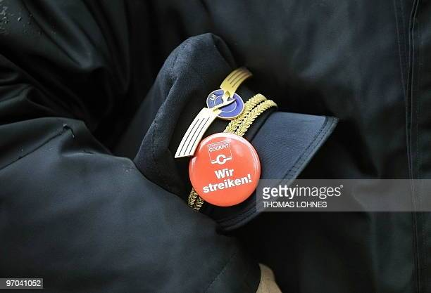 A pilot of German airline Lufthansa holds his hat under his arm with a badge which reads 'We are on strike' during a strike at the airport in the...