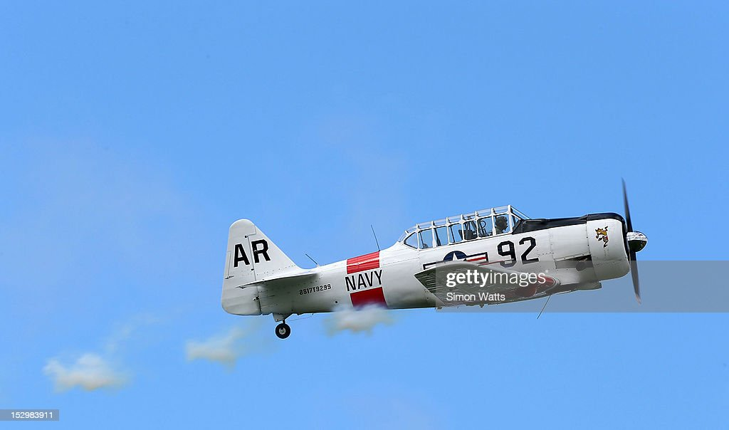 A pilot performs aerobatics in a vintage Harvard aircraft during an airshow commemorating the completion of the the rebuild of de Havilland Mosquito KA 114, on September 29, 2012 in Ardmore, New Zealand. The plane was restored by Warbird Restorations at Ardmore Aerodrome and is the only flying Mosquito in the world.