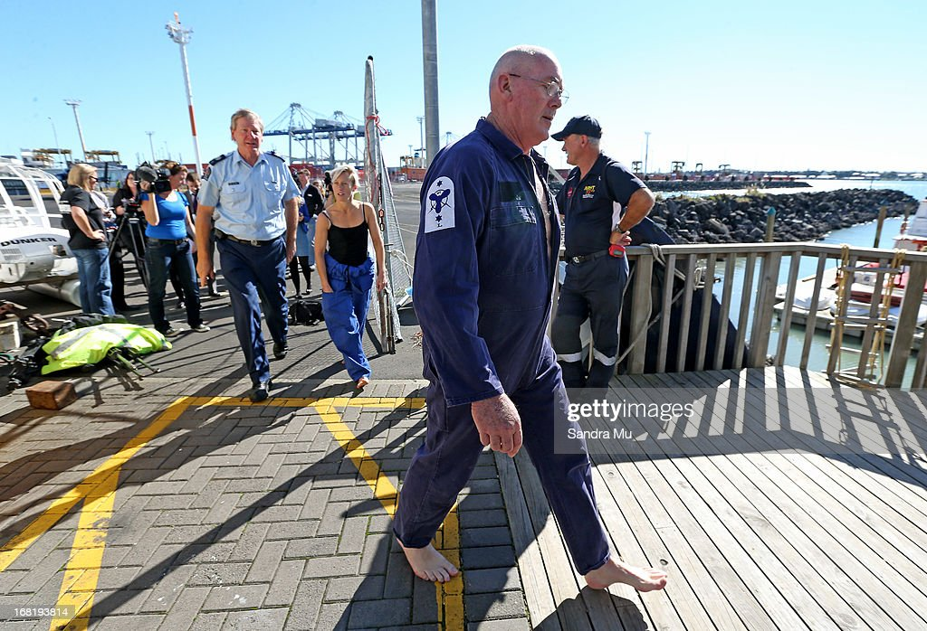 Pilot Peter Maloney walks bacl to base with engineer Nina Heatley following after they spoke to media after being rescued from Waitemata Harbour after a helicopter crash on May 7, 2013 in Auckland, New Zealand. Both the pilot and a crew member - the only two on board walked away unscathed after their helicopter crashed into Waitemata Harbour in Auckland today. The two were resuced by the navy after the helicopter reportedly lost power and plummeted into the sea.