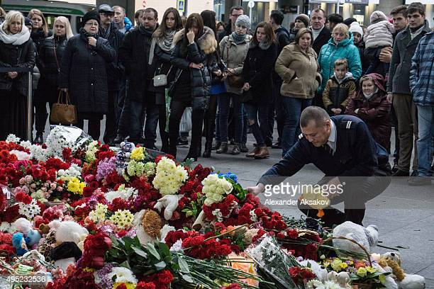 A pilot places flowers in memory of the victims of Airbus A321 crash at the Pulkovo Airport on November 1 2015 in St Petersburg Russia A Russian...