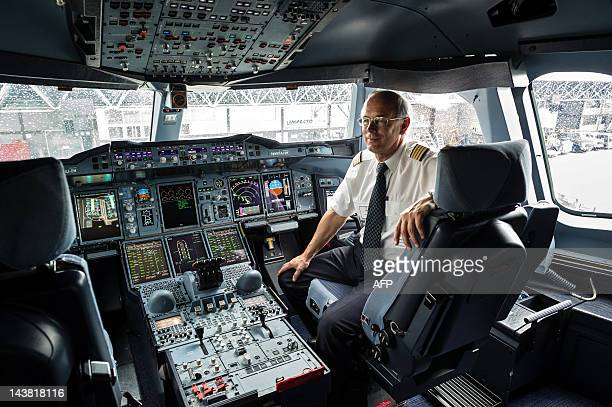 A pilot poses at the cockpit of European aircraft manufacturer Airbus' A380 the world's largest doubledeck jet airliner at Guarulhos international...