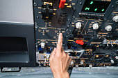 Pilot pushing buttons in the cockpit