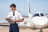 Pilot Reviewing Log Book Near Corporate Jet