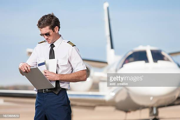 Pilot Reviewing Log Book Near Corporate Jet