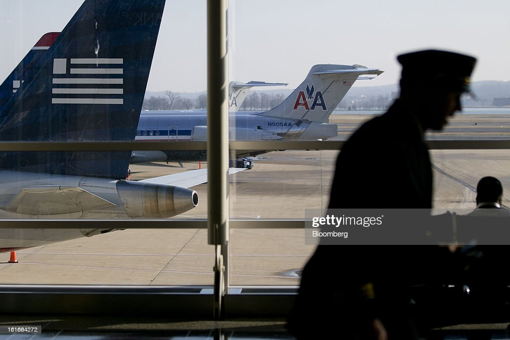 A pilot runs past US Airways Group Inc. and AMR Corp.'s American Airlines airplanes parked on the tarmac at Reagan National Airport in Washington, D.C., U.S., on Thursday, Feb. 14, 2013. US Airways Group Inc., spurned in three prior merger attempts, will combine with bankrupt AMR Corp.'s American Airlines in an $11 billion deal to create the world's largest carrier. Photographer: Andrew Harrer/Bloomberg via Getty Images