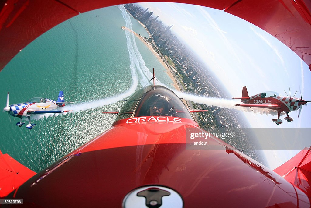 Pilot Sean Tucker (C), his son Eric (R) and Ben Freelove fly their aircraft over Lake Michigan as they prepare for this weekend's Chicago Air and Water Show August 14, 2008 in Chicago, Illinois. The three along with pilot Bill Stein will perform as the Collaborators formation aerobatic team during the show.