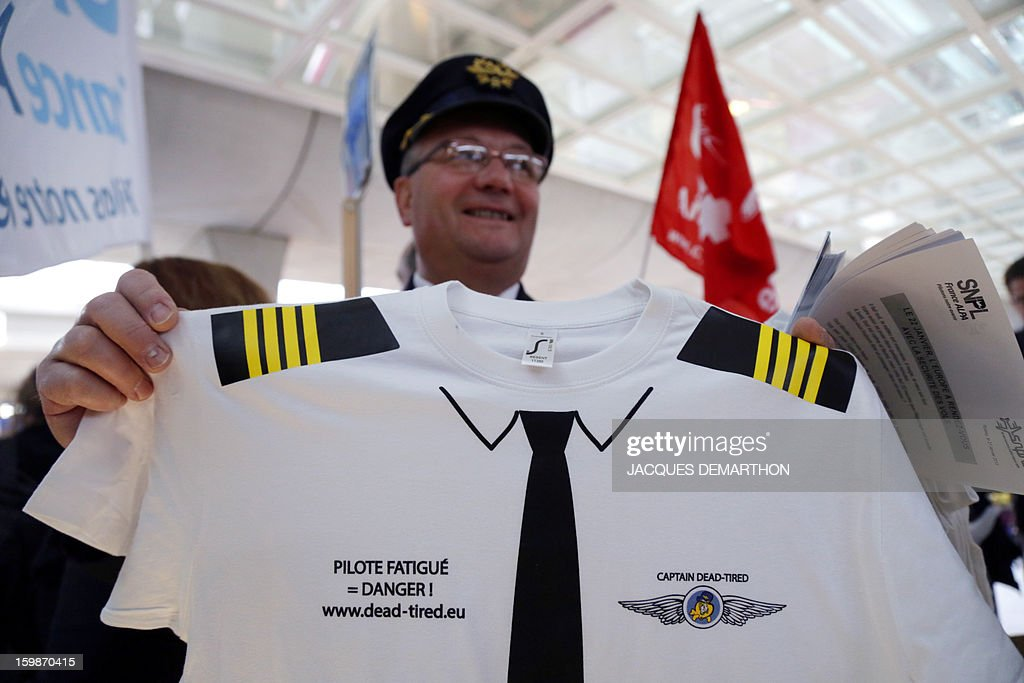 A pilot shows a T-shirt reading 'Captain dead-tired = Danger' during a demonstration held by pilots and cabin crew members of European airline companies, on January 22, 2013 at Roissy Charles-de-Gaulle airport, in Roissy-en-France outside Paris, as part of a strike of European pilots.