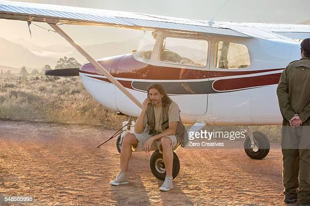 Pilot sitting beside plane, Wellington, Western Cape, South Africa