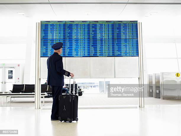 Pilot standing and looking at departure board