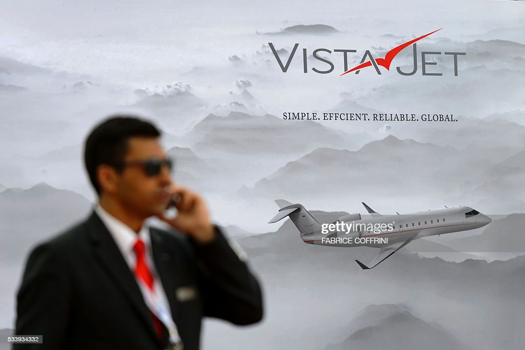 A pilot talks on his mobile phone at the stand of the Swiss private business jet charter VistaJet during the European Business Aviation Convention & Exhibition (EBACE) on May 24, 2016 in Geneva. COFFRINI