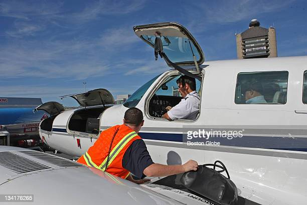 Pilot Tom Garlington seated in the plane waits for baggage to loaded in the wing and front portion of the plane CapeAir's fall introduction of...