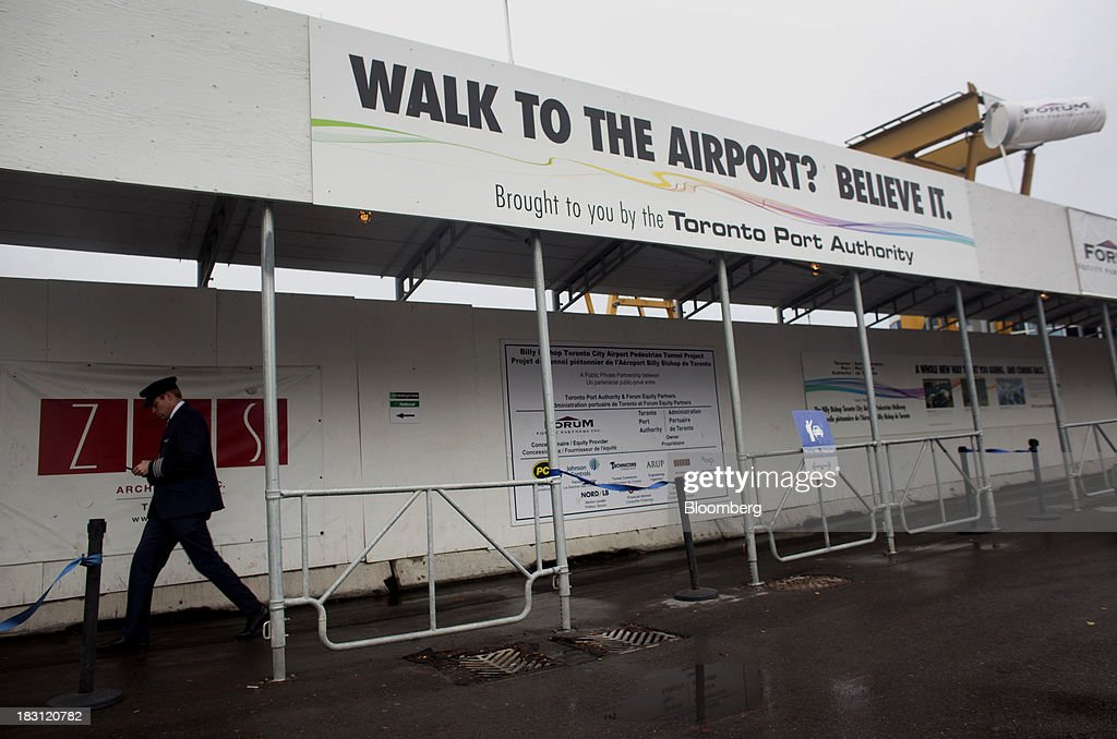 A pilot walks by advertising for the Billy Bishop Toronto City Airport pedestrian tunnel in Toronto, Ontario, Canada, on Friday, Oct. 4, 2013. The tunnel, which connects the Toronto mainland at the foot of Eireann Quay to the airport terminal, will have moving sidewalks, an elevator at both ends, and an escalator on the island side. Photographer: Brett Gundlock/Bloomberg via Getty Images