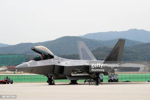 A pilot waves as he sits in a US Air Force F22 Raptor fighter jet manufactured by Lockheed Martin Corp during a press day of the Seoul International...