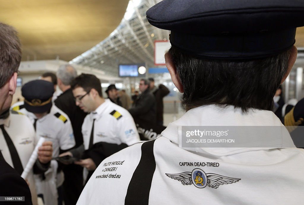 A pilot wearing a T-shirt reading 'Captain dead-tired' takes part in a demonstration with pilots and cabin crew members of European airline companies, on January 22, 2013 at Roissy Charles-de-Gaulle airport, in Roissy-en-France outside Paris, as part of a strike of European pilots.