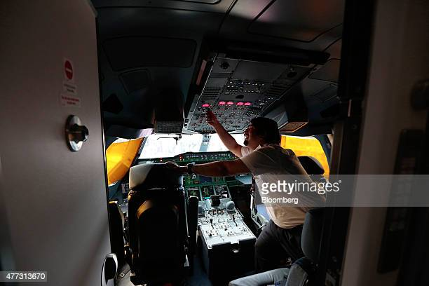 A pilot works in the cockpit beyond the cockpit access door of an Airbus SAS A380 aircraft operated by Qatar Airways Ltd on day two of the 51st...