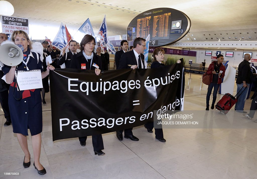 Pilots and cabin crew members of European airline companies hold a banner reading 'Dead-tired crews. Passengers in danger' during a demonstration, on January 22, 2013 at Roissy Charles-de-Gaulle airport, in Roissy-en-France outside Paris, as part of a strike of European pilots. AFP PHOTO JACQUES DEMARTHON