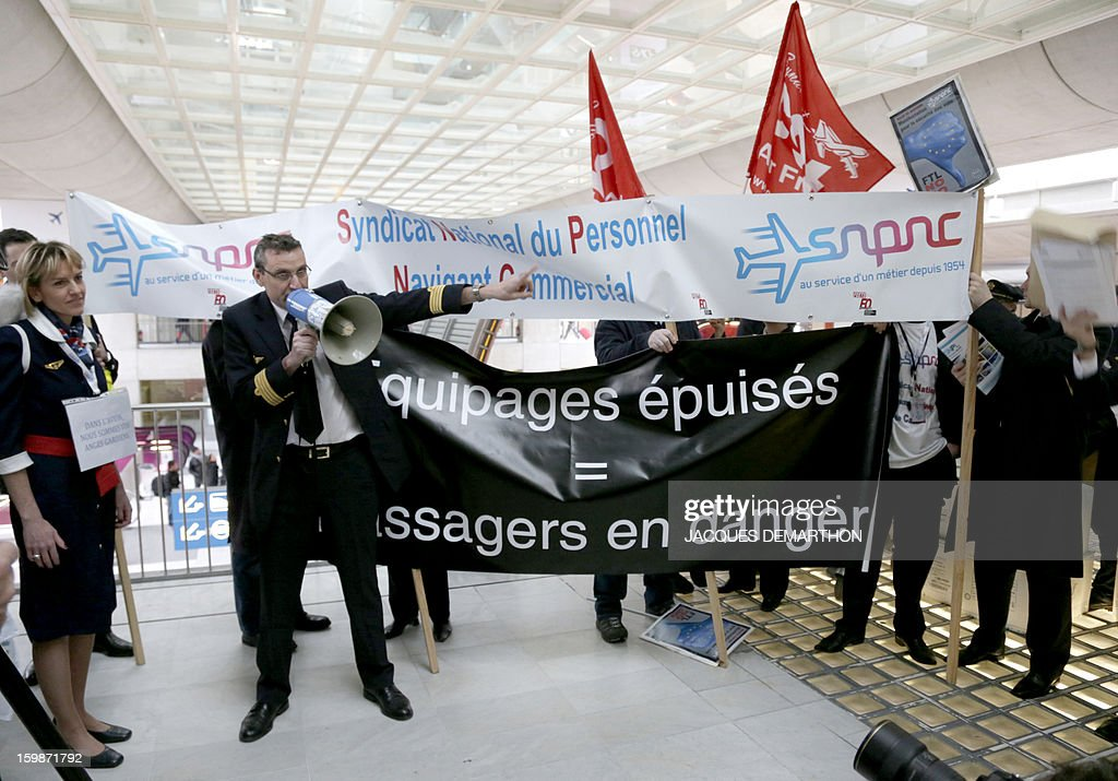 Pilots and cabin crew members of European airline companies hold a banner reading 'Dead-tired crews. Passengers in danger' during a demosntration, on January 22, 2013 at Roissy Charles-de-Gaulle airport, in Roissy-en-France outside Paris, as part of a strike of European pilots. AFP PHOTO JACQUES DEMARTHON