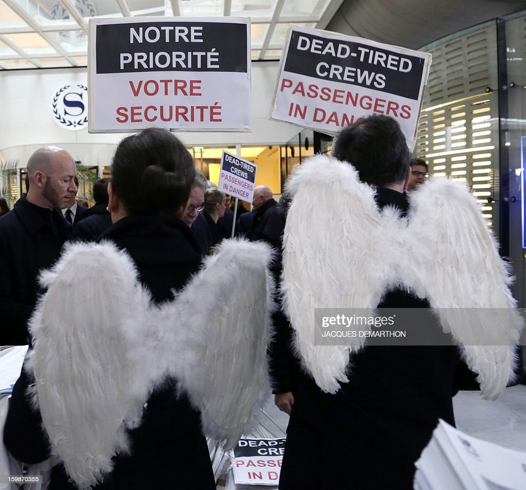 Pilots and cabin crew members of European airline companies, including two of them wearing 'angel wings', hold placards reading 'Dead-tired crews. Passengers in danger' during a demonstration on January 22, 2013 at Roissy Charles-de-Gaulle airport, in Roissy-en-France outside Paris, as part of a strike of European pilots. AFP PHOTO JACQUES DEMARTHON