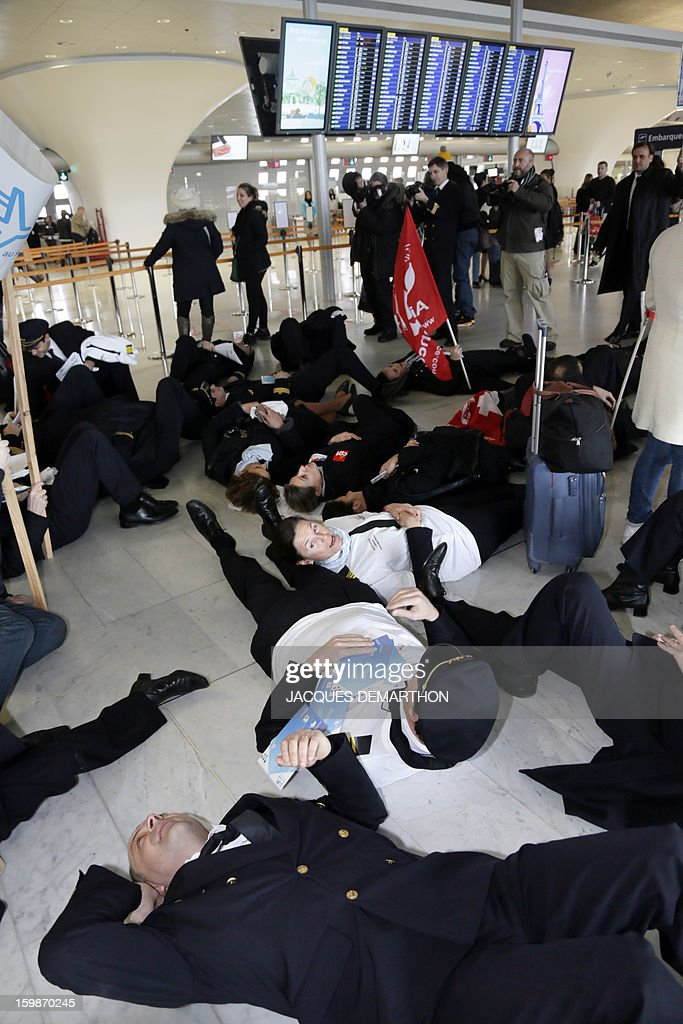 Pilots and cabin crew members of European airline companies take part in a sit-in during a demonstration, on January 22, 2013 at Roissy Charles-de-Gaulle airport, in Roissy-en-France outside Paris, as part of a strike of European pilots.