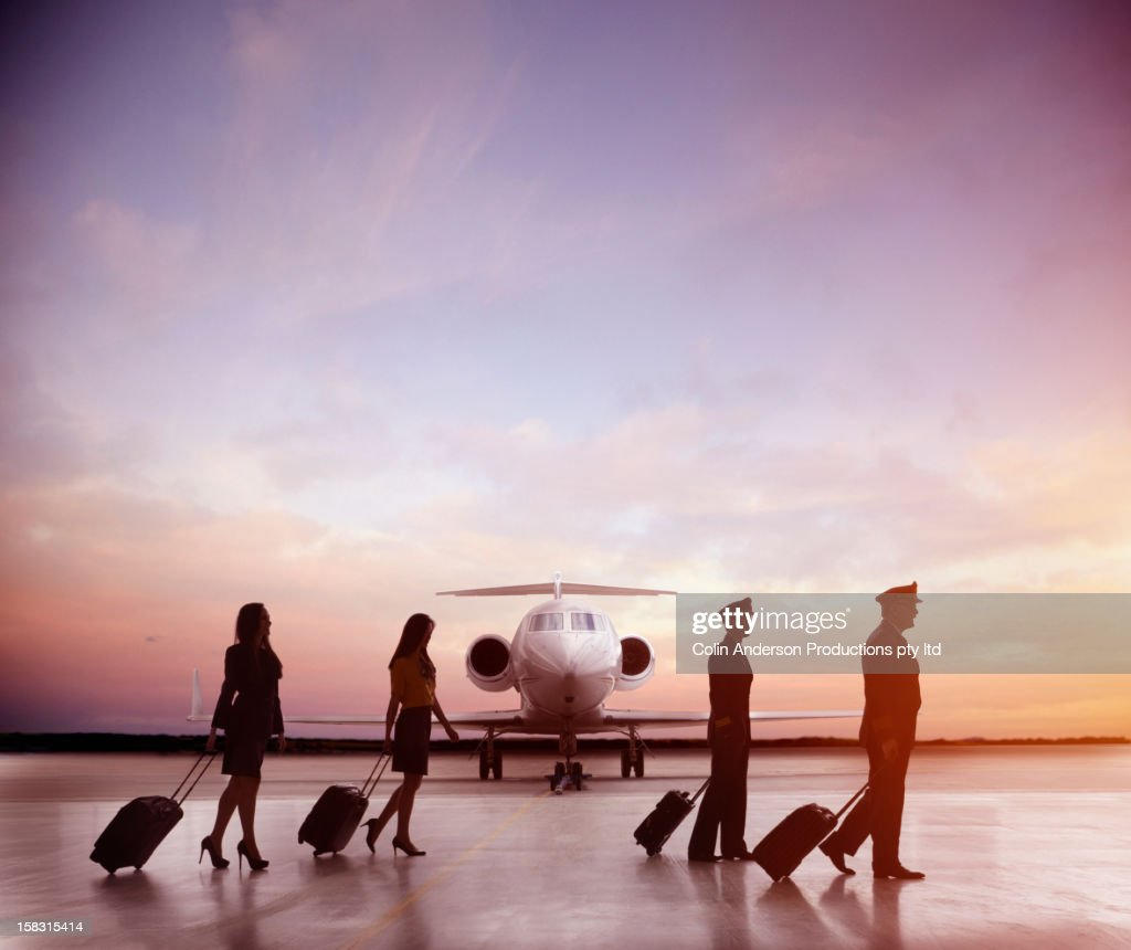Pilots and flight staff walking near jet : Stock Photo