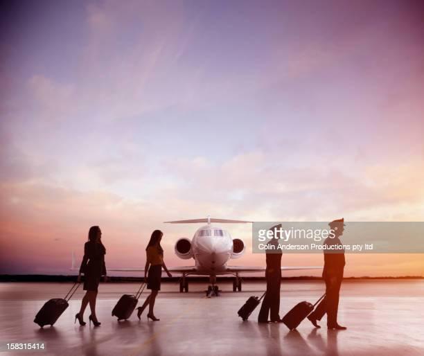 Pilots and flight staff walking near jet