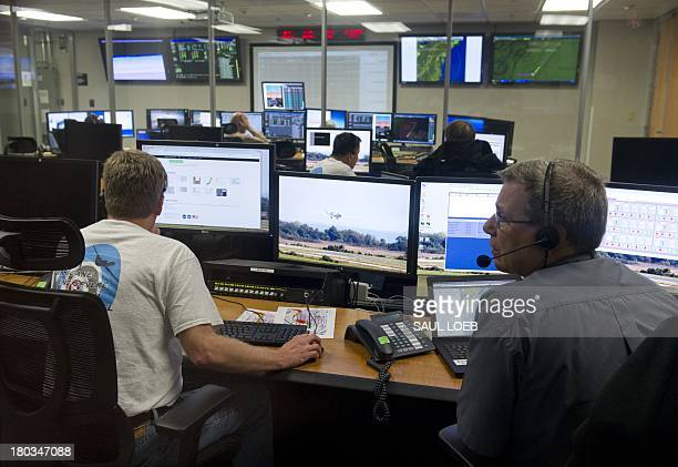Pilots and scientists monitor a NASA Global Hawk unmanned aerial vehicle or drone aircraft from a mission control center inside an airplane hangar...