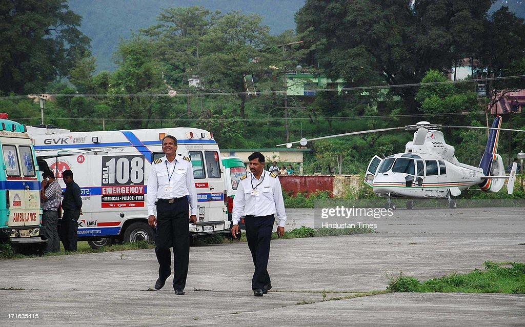 Pilots coming out of the Helicopter after landing at Doon Helidrome on June 27, 2013 in Dehradun, India. Air rescue operations resumed today to pull out stranded people but they had to be halted for Badrinath as the weather turned bad, even as decaying bodies were being cremated swiftly in worst-hit Kedarnath Valley amid fears of an epidemic outbreak.