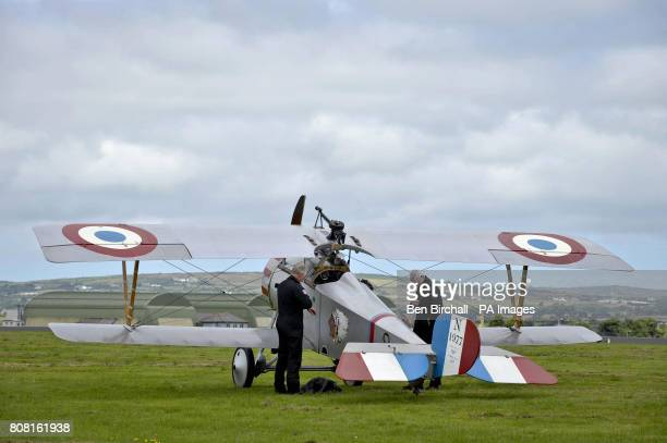 Pilots from the Great War Display Team prepare for flight as they suit up next to a Nieuport single seat fighter a classic marque of the 191418 war...