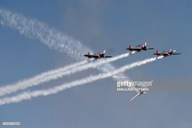 Pilots of Britain's aerobatic team 'Yakovlevs' perform aerial stunts during a display on the third day of the 11th edition of 'Aero India' a biennial...