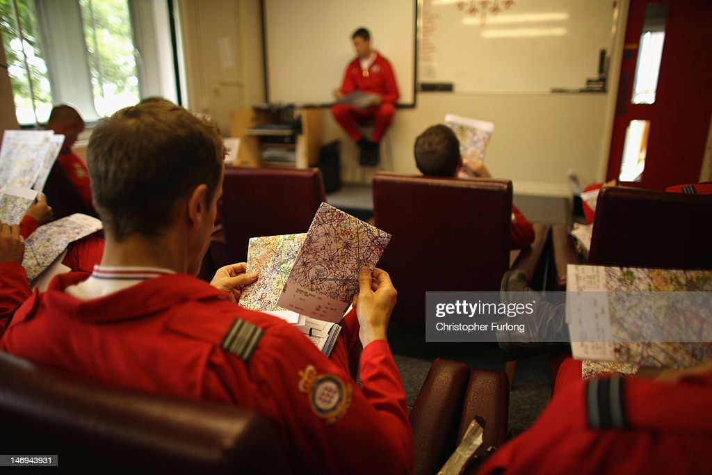 Pilots of the Red Arrows display team listen to a pre-flight briefing at RAF Scampton on June 22, 2012 in Scampton, England. The famous Royal Air Force Red Arrows are perfecting their routine for a fly past next week when the Olympic torch arrives in Norfolk and also for an audience of millions during the opening ceremony of the London 2012 Olympics.
