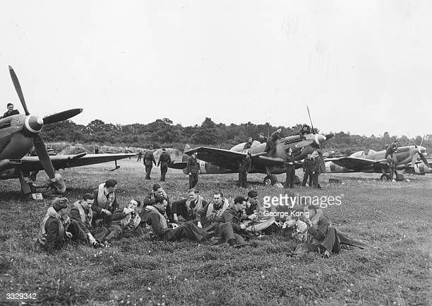 Pilots who took part in the Battle of Britain waiting by their Spitfires for the 'scramble' as part of a reenactment for a television broadcast
