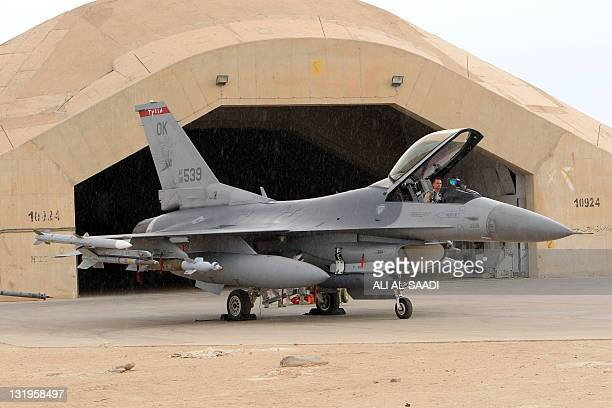 A pilotsits in a US F16 jet fighter at the alAsad Air Base west the capital Baghdad as soldiers begin to begin their journey home out of Iraq on...