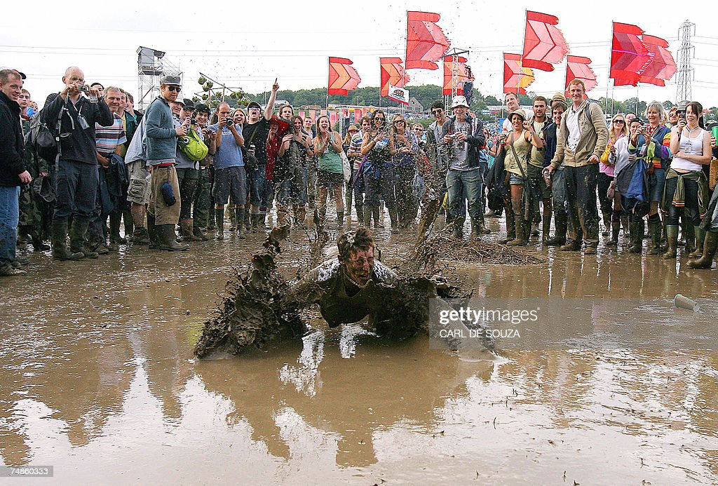 A music fan slides in the mud, at Glastonbury music festival, Pilton, Somerset, 22 June 2007. 177,500 people are expected to attend the annual outdoor festival despite wet weather being predicted for all the duration of the festival.