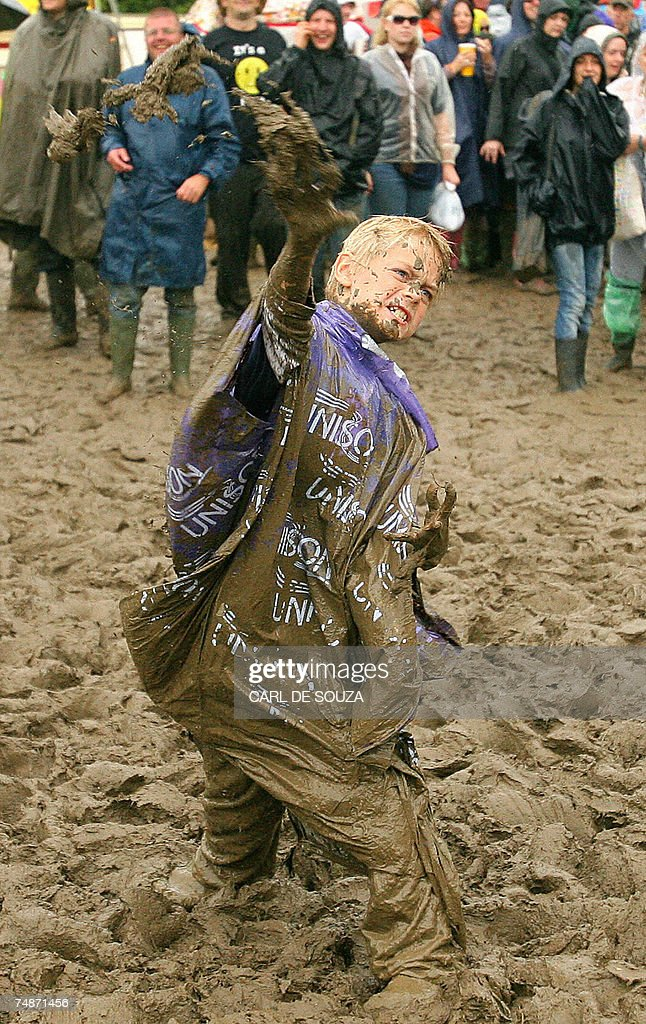 A young reveller throws mud at the crowds near the Pyramid stage at Glastonbury music festival, Pilton, Somerset 23 June 2007. 177,500 people are expected to attend the annual outdoor festival. Wet weather has been predicted for the duration of the festival. AFP PHOTO/CARL DE SOUZA