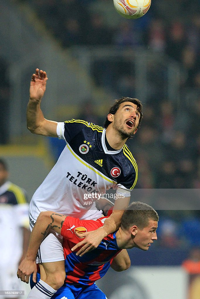 Pilzen´s defender Lukas Hejda (down) fights for the ball with Fenerbahce's midfielder Mehmet Topal (up) during the UEFA Europa League Round of 16 first leg football match FC Viktoria Plzen vs Fenerbahce SK in Plzen, Czech Republic, on March 7, 2013.
