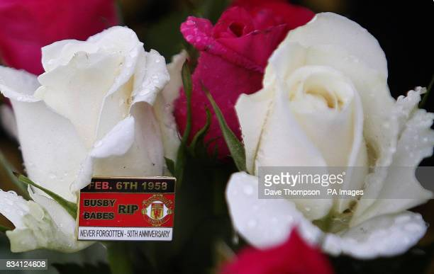 A pin badge on some flowers at the grave of Sir Matt Busby who was the manager of Manchester United at the time of the Munich air disaster Manchester