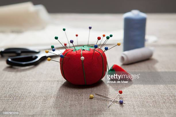 Pin cushion, thread and scissors