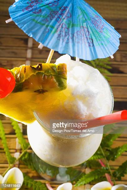 A pina colada garnished with fruit and flowers.