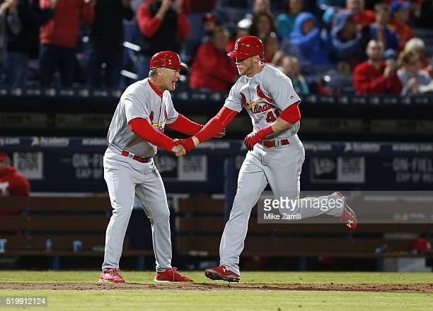 Pinch hitter Jeremy Hazelbaker of the St Louis Cardinals is congratulated by third base coach Chris Maloney after Hazelbaker's seventh inning home...