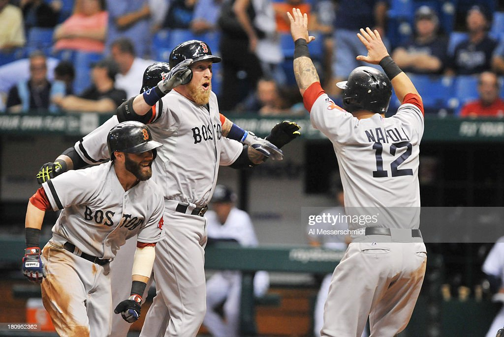 Pinch hitter Mike Carp #37 (middle) of the Boston Red Sox celebrates after a grand slam home run in the 10th inning against the Tampa Bay Rays September 11, 2013 at Tropicana Field in St. Petersburg, Florida. Boston won 7 - 3.