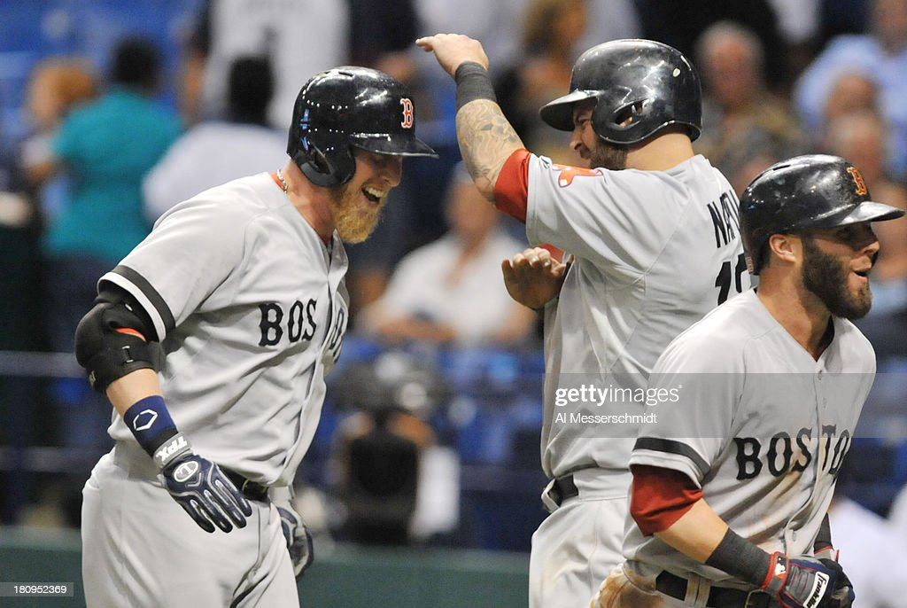 Pinch hitter Mike Carp #37 (left) of the Boston Red Sox celebrates after a grand slam home run in the 10th inning against the Tampa Bay Rays September 11, 2013 at Tropicana Field in St. Petersburg, Florida. Boston won 7 - 3.