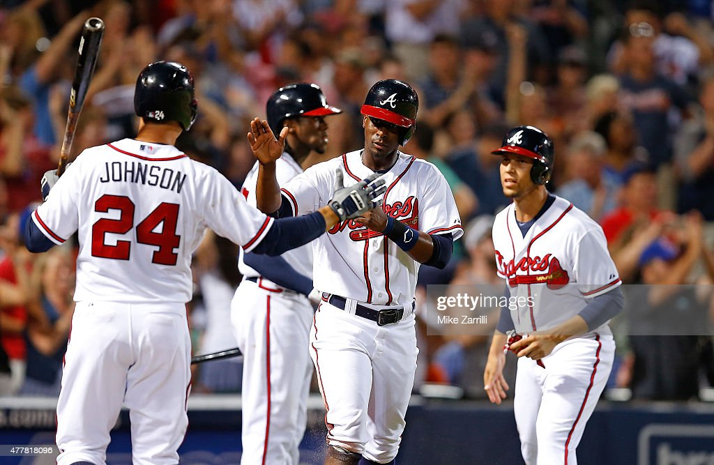 Pinch hitter Pedro Ciriaco of the Atlanta Braves is congratulated by third baseman Chris Johnson while Andrelton Simmons and Cameron Maybin look on...