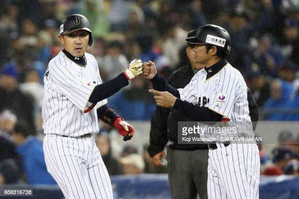 Pinch hitter Seiichi Uchikawa of Japan high fives with Coach Toshihisa Nishi after hitting a single in the bottom of the eighth inning during the...