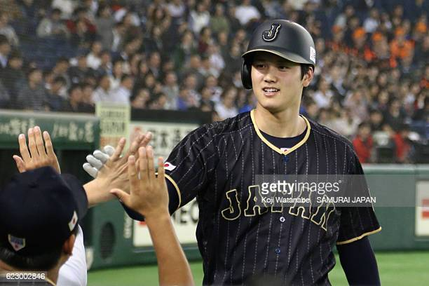 Pinch hitter Shohei Ohtani of Japan high fives after scoring by a RBI double by Infielder Ryosuke Kikuchi in the seventh inning during the...