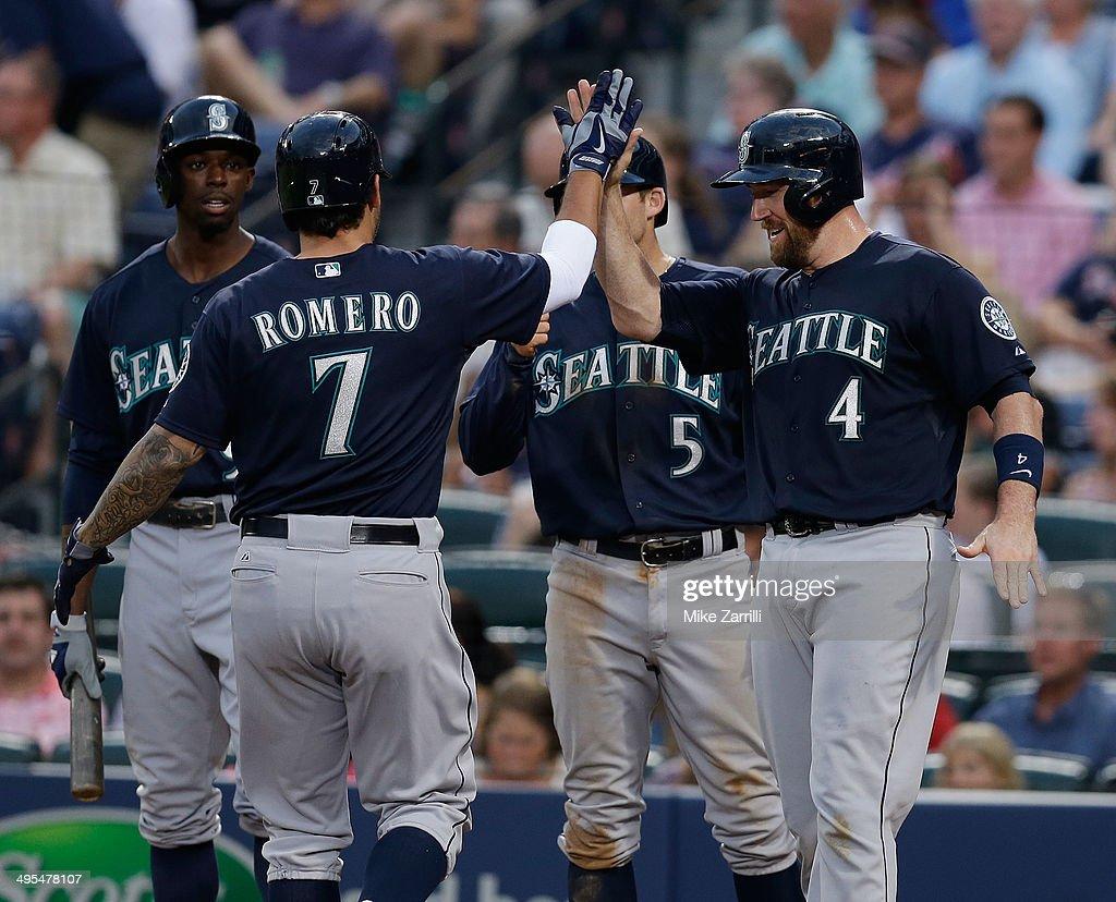 Pinch hitter Stefen Romero of the Seattle Mariners is congratulated by teammates catcher John Buck shortstop Brad Miller and centerfielder James...