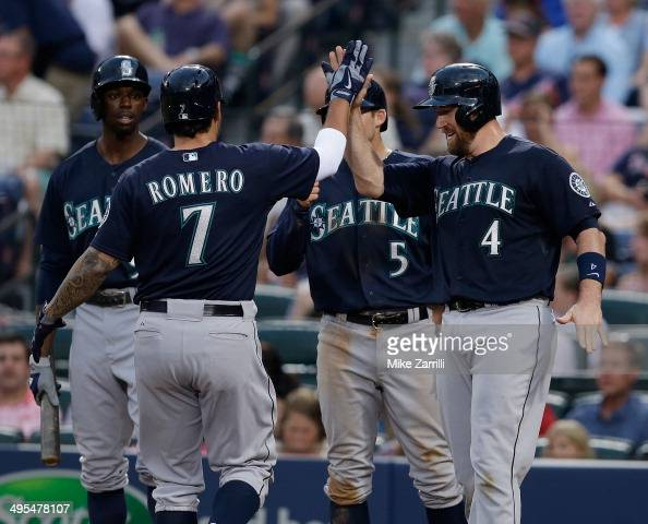 Pinch hitter Stefen Romero of the Seattle Mariners is congratulated by teammates catcher John Buck shortstop Brad Miller and centerfielder James...