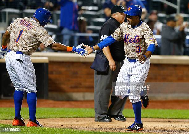 Pinch runner Eric Young Jr #1 and Curtis Granderson of the New York Mets after both scored in the seventh inning inning against the Atlanta Braves...