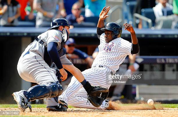 Pinch runner Jose Pirela of the New York Yankees slides home to score the game winning run in the ninth inning as Curt Casali of the Tampa Bay Rays...